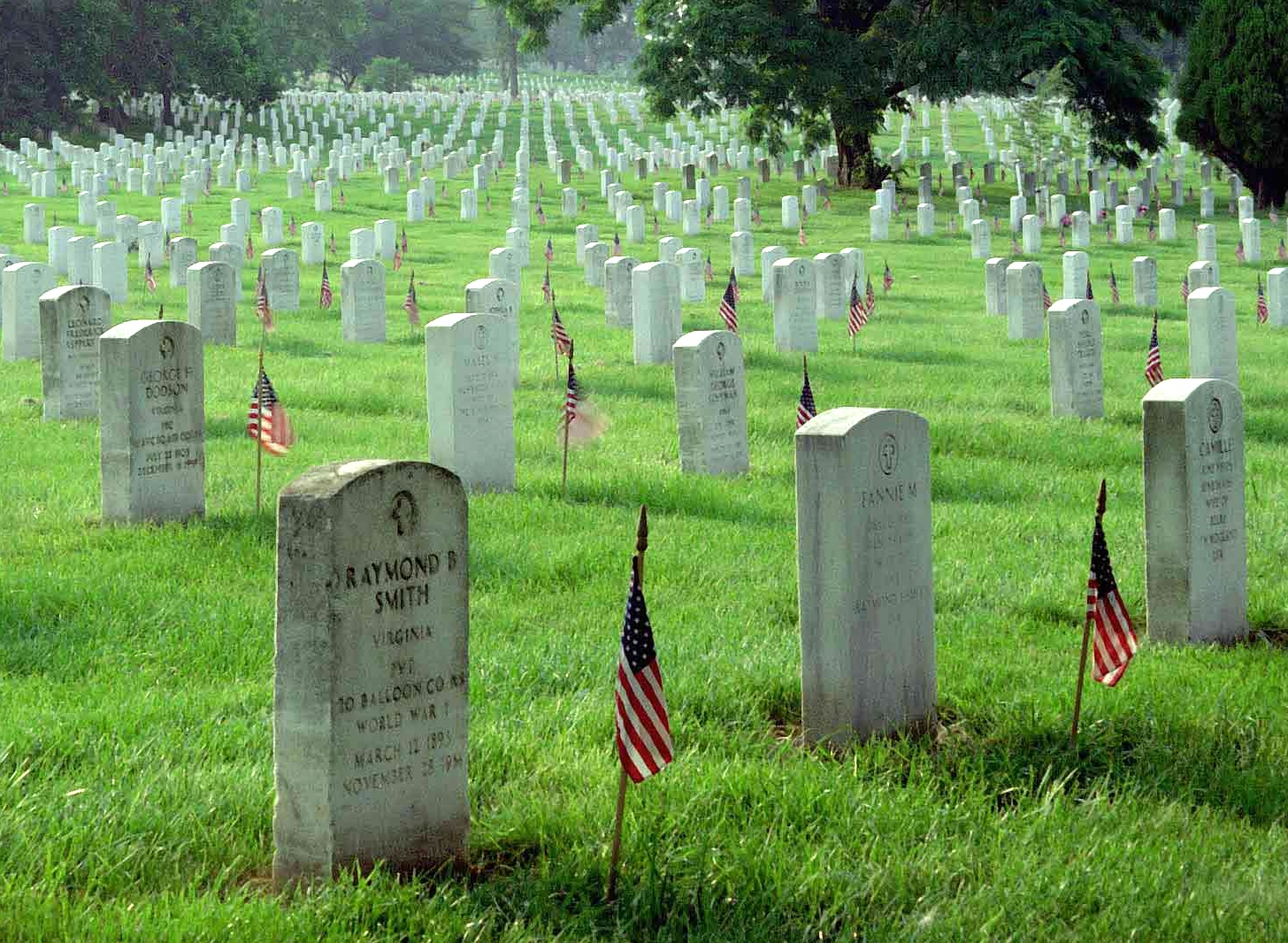 pictures of gravestones at Arlington with US flags for Memorial Day